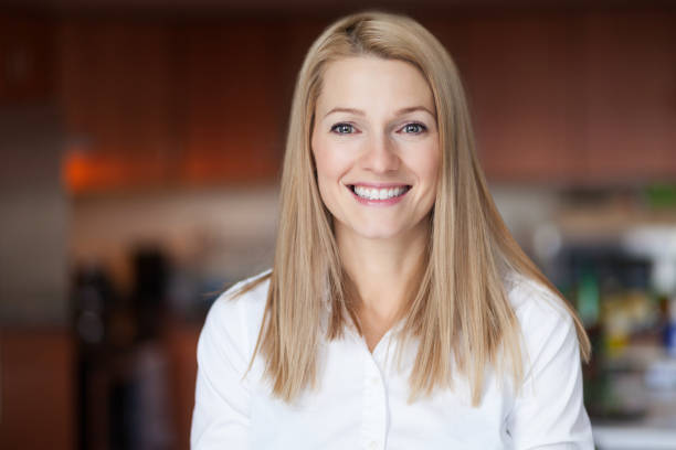 Close up Of A Smiling Caucasien blond woman in the kitchen at the office stock photo