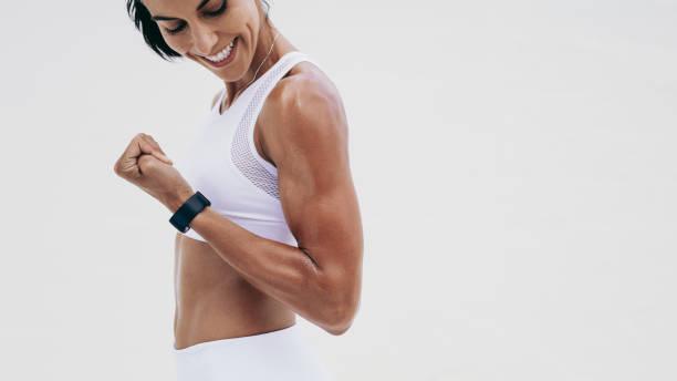 一個面帶微笑的健身女人靠近她的手 - 肌肉發達 個照片及圖片檔