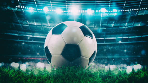 Close up of a soccer ball in the center of the stadium illuminated by the headlights - foto stock