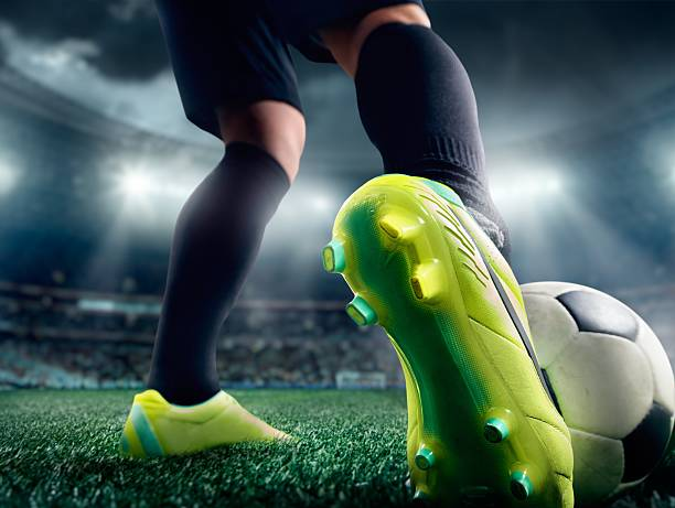 Close up of a soccer player's foot in a stadium stock photo