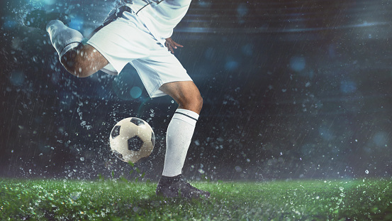 Close up of a soccer scene at night match with player in a white uniform kicking the ball with power