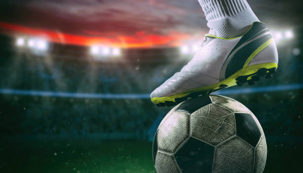 Close up of a soccer striker ready to kicks the ball at the stadium - foto stock