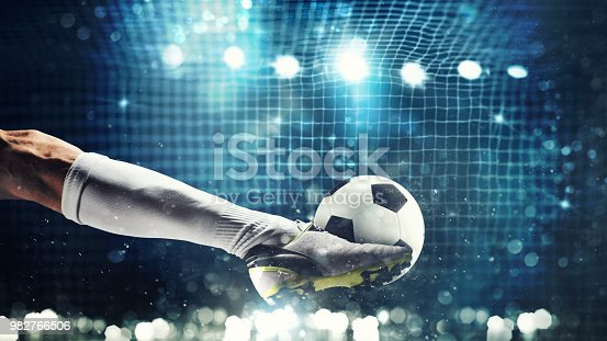 istock Close up of a soccer striker ready to kicks the ball in the football goal 982766506