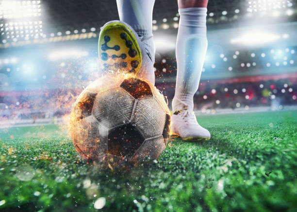 Close up of a soccer striker ready to kicks the fiery ball at the stadium stock photo