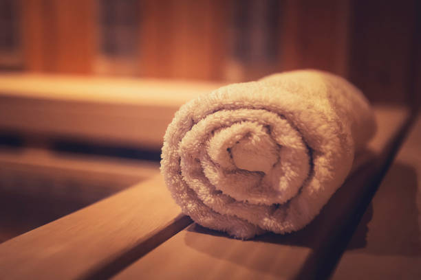 a close up of a soft terry bath towel in a wooden steam sauna. comfortable rest in a traditional russian cedar bath. execellent conviniences for relaxation in steam room of eco-designed sauna. - sauna foto e immagini stock
