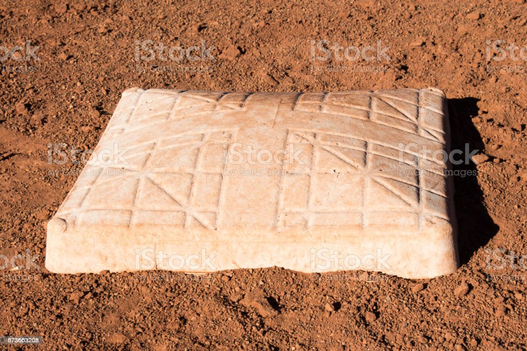Close up of a softball base in the dirt stock photo
