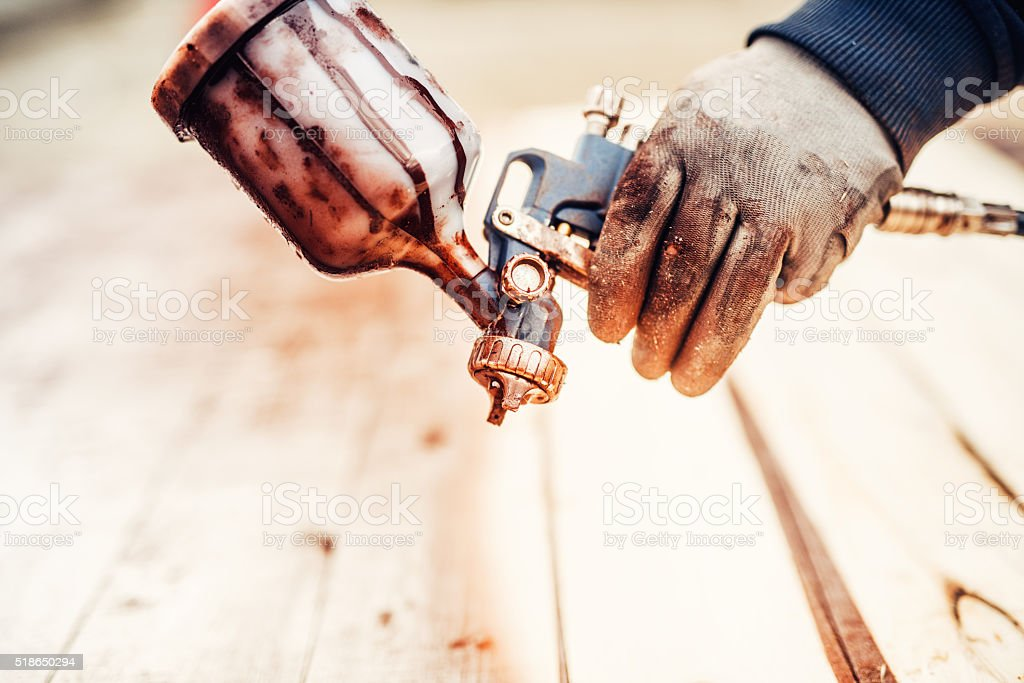 Close up of a spray paint gun and worker hand stock photo