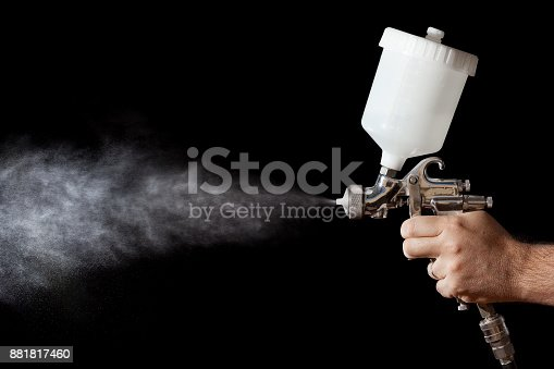 istock Close up of a spray paint gun with black background 881817460