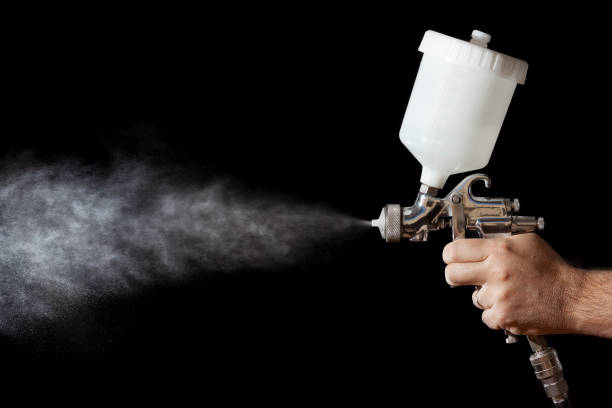 Close up of a spray paint gun with black background Close up of a spray paint gun with black background pistol stock pictures, royalty-free photos & images