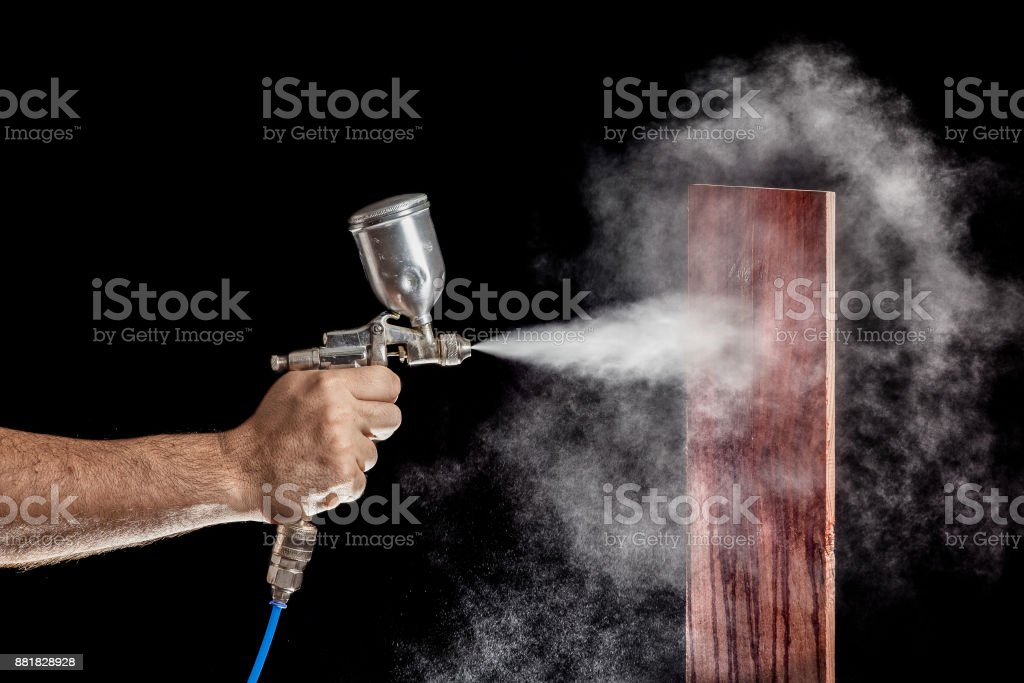 Close up of a spray paint gun with brown background stock photo