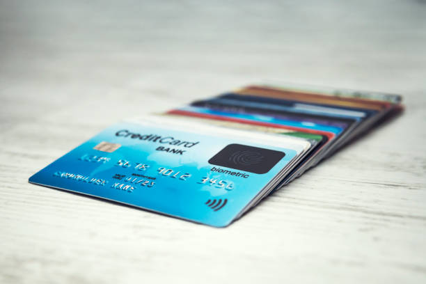 Close up of a stack of credit cards lying in order on the white table top. Many different credit cards with biometric card on top. Shopping with biometric scanning technology. Cardholder security. stock photo