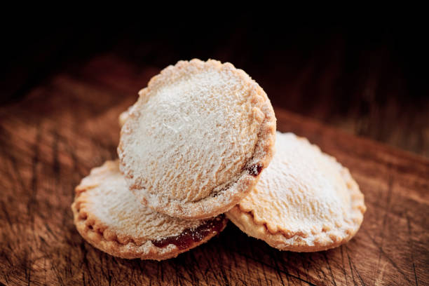 Close up of a stack of Mince Pies on a dark rustic wooden surface. stock photo