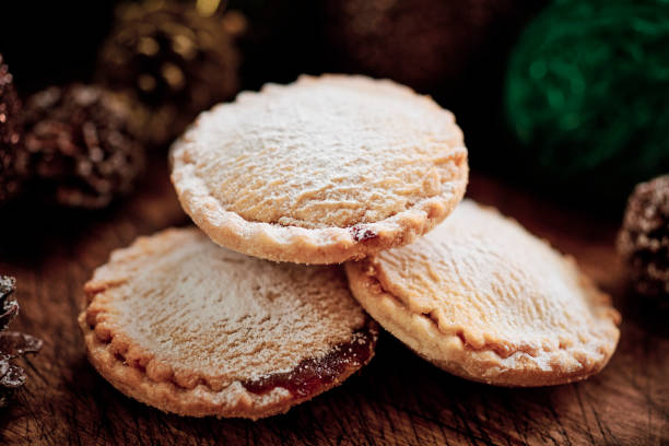 Close up of a stack of Mince Pies on a dark rustic wooden surface with pine cones and christmas decorations. stock photo