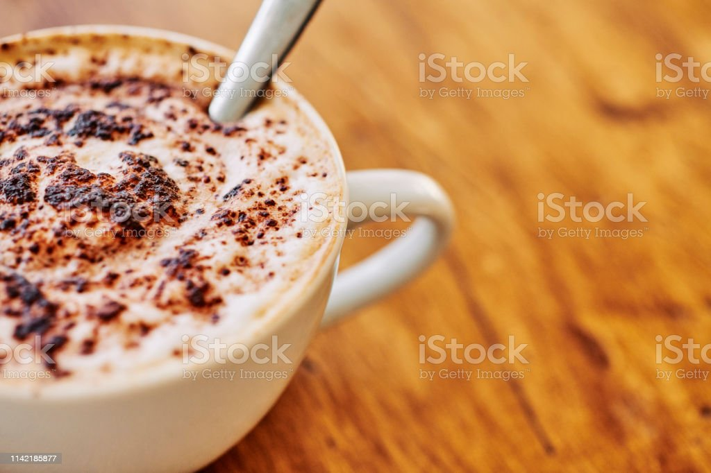 Close up of a stirred Cappuccino with room for copy. stock photo