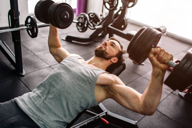 Close up of a strong man doing push ups with the dumbbells. He is consentrated only on doing that exercise and on nothing else. Cut view. Close up of a strong man doing push ups with the dumbells. He is consentrated only on doing that exercise and on nothing else. Cut view macho stock pictures, royalty-free photos & images