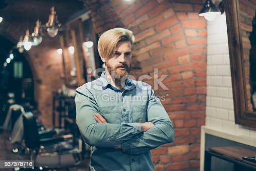 698023272 istock photo Close up of a stunning look of a red bearded blond guy with trendy hairdo in a barber shop. Looking so fashionable and confident, harsh and severe 937378716