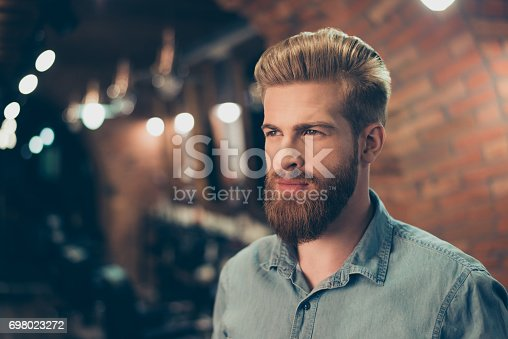 istock Close up of a stunning look of a red bearded guy with trendy hairdo in a barber shop. Looking so fashionable and confident 698023272