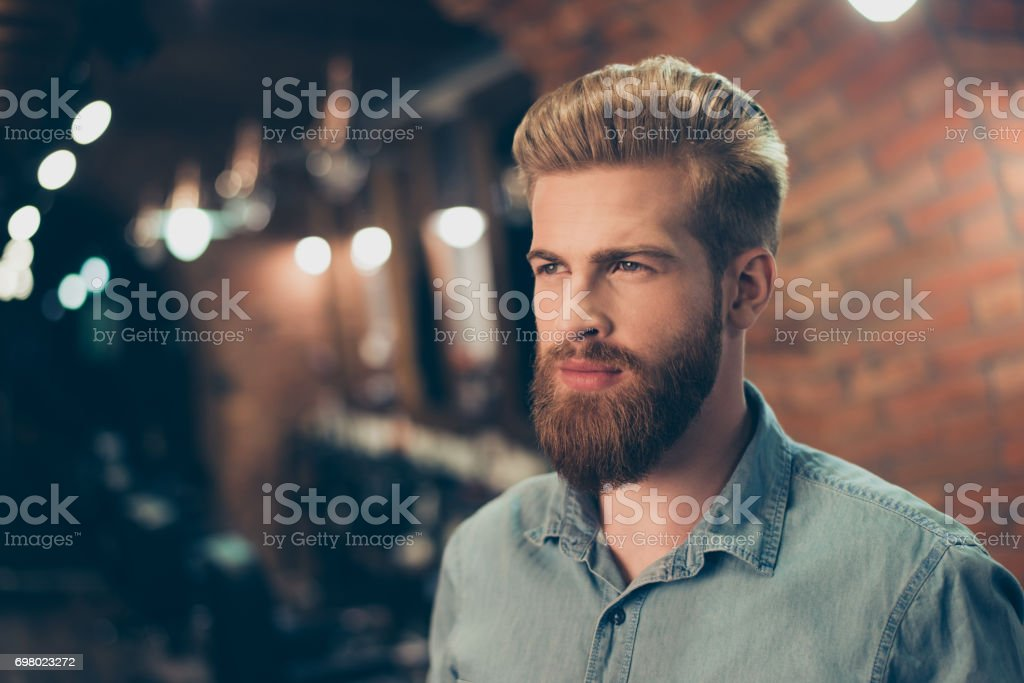 Close up of a stunning look of a red bearded guy with trendy hairdo in a barber shop. Looking so fashionable and confident stock photo