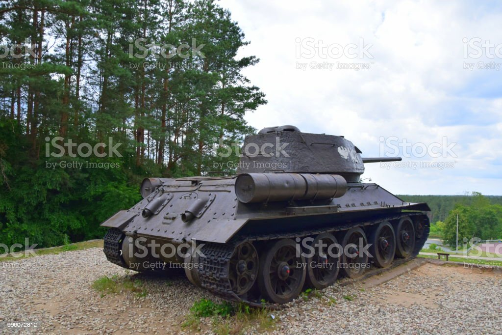 Close up of a tank replica standing on a high hill with the view on the forest, car park, bridge and a river with cloudy sky above the scene seen in summer during exploration stock photo