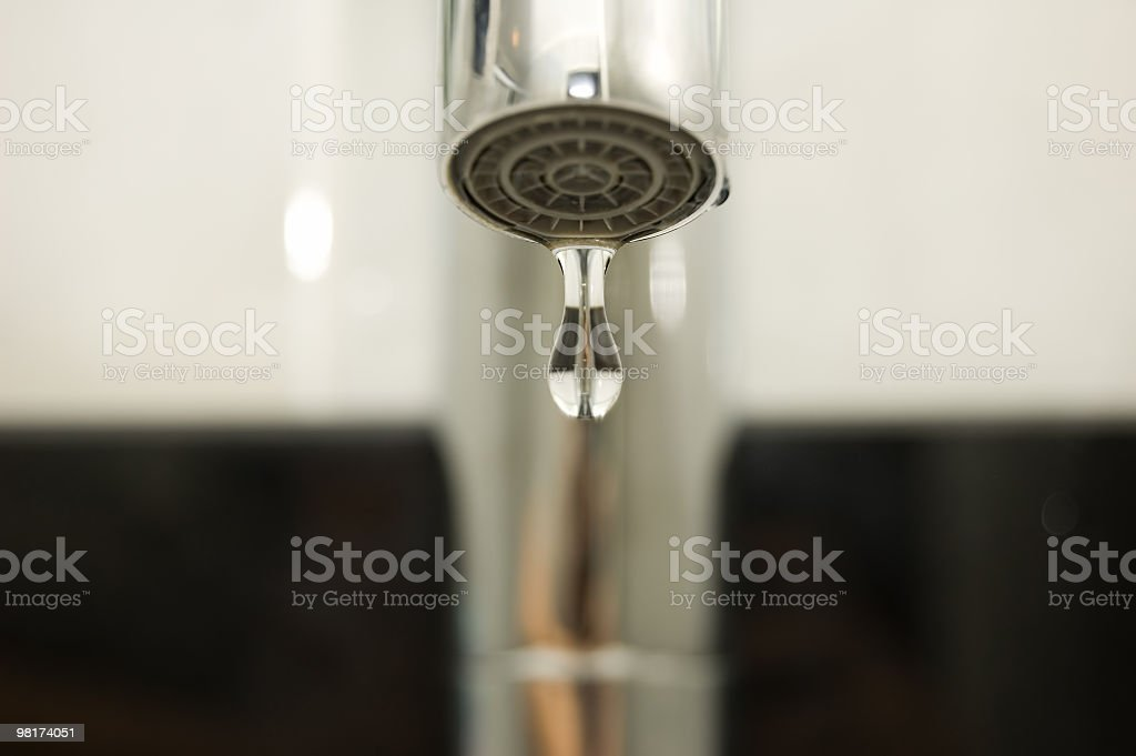 A close up of a tap with a water drip coming out of it royalty-free stock photo