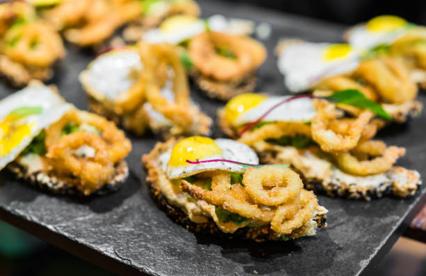 Close up of a tapa with bread, fried squid calamari, quail egg, and greens at a street food market fair festival Close up of a tapa with bread, fried squid calamari, quail egg, and greens at a street food market fair festival food festival stock pictures, royalty-free photos & images