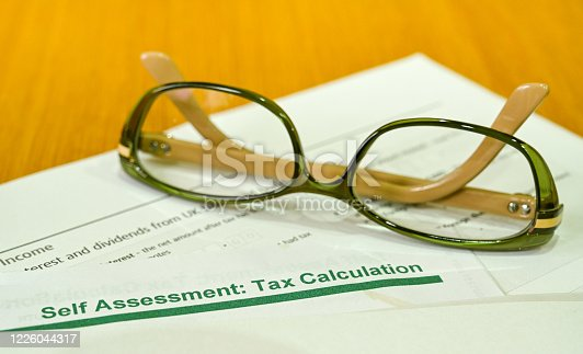 Pair of reading glasses on top of a tax assessment self assessment calculation notice issued by Her Majesty's Revenue & Customs in the UK. Some taxpayers are required to complete annual self-assessments and submit a tax return