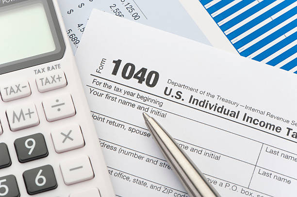 Close up of a Tax return form Close up of a Tax return form with calculator 1040 tax form stock pictures, royalty-free photos & images