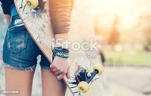 Rear view of teenage girl with skateboard in the park