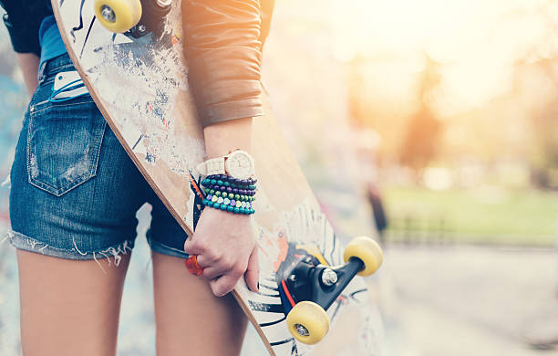 Close up of a teenage girl holding skateboard stock photo