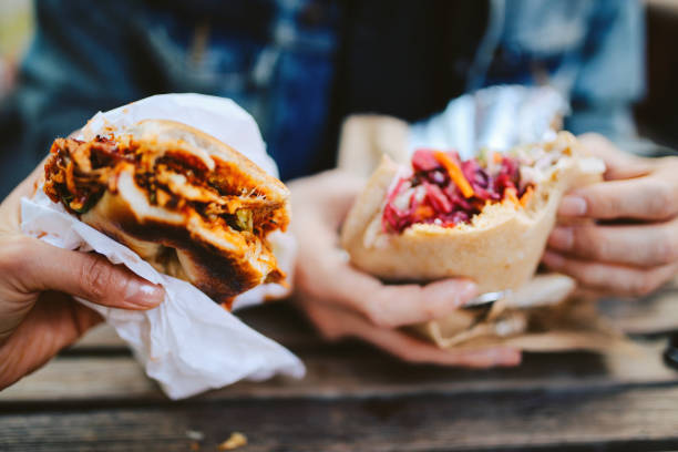 Close up of a Texas pulled pork bbq burger and a falafel outdoors stock photo