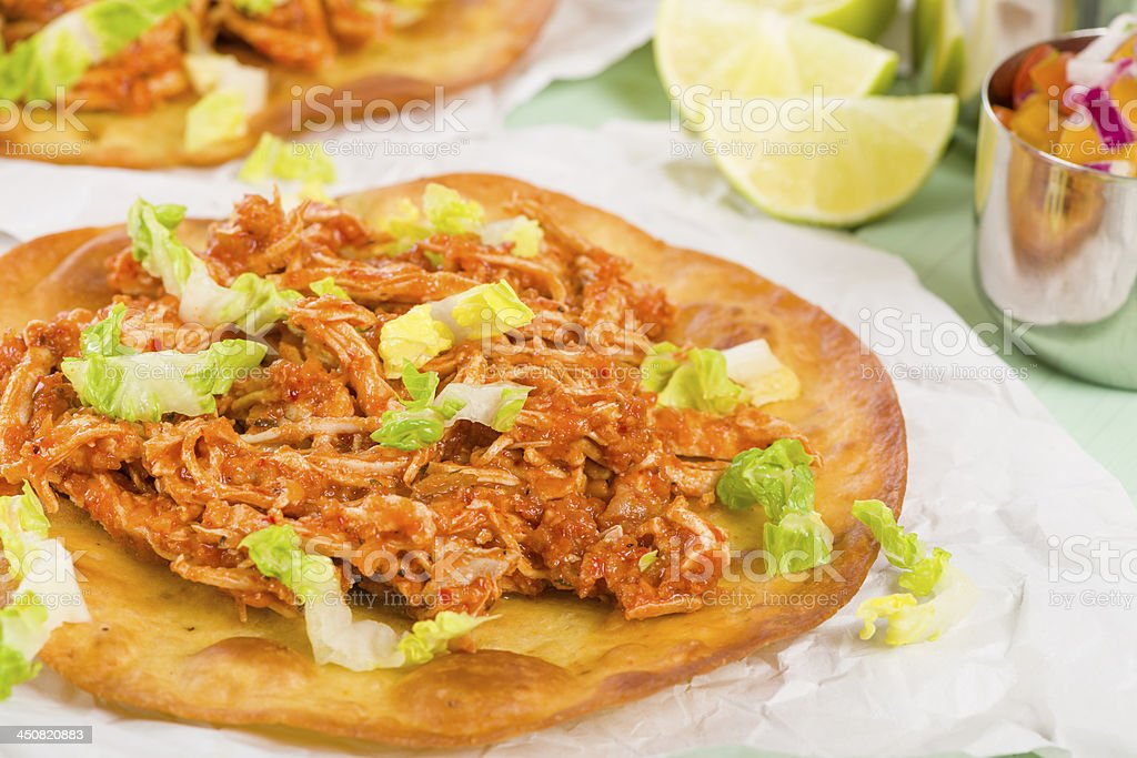 A close up of a tostada with shredded lettuce stock photo