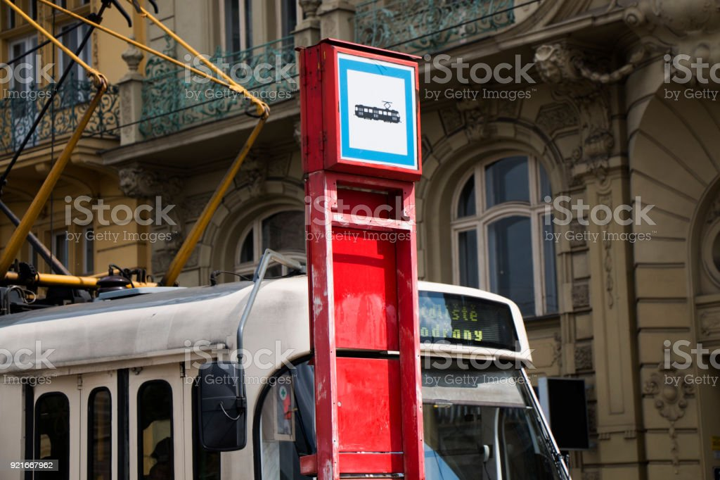 Close up of a tram stop sign with waiting tra and buildings in the background stock photo