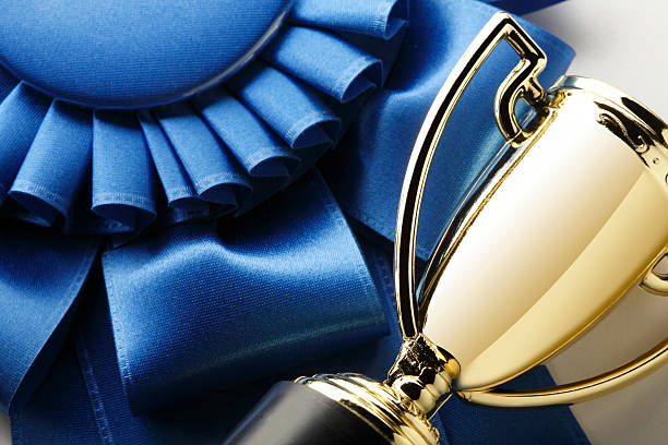 close up of a trophy and a blue ribbon - trophy award stock photos and pictures