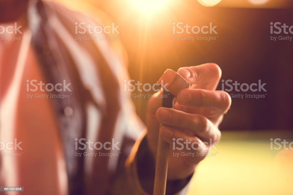 Close up of a unrecognizable man chalking pool cue. stock photo