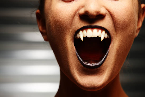 Close up of a vampire woman's mouth Close up of a vampire woman's mouth over dark background fang stock pictures, royalty-free photos & images