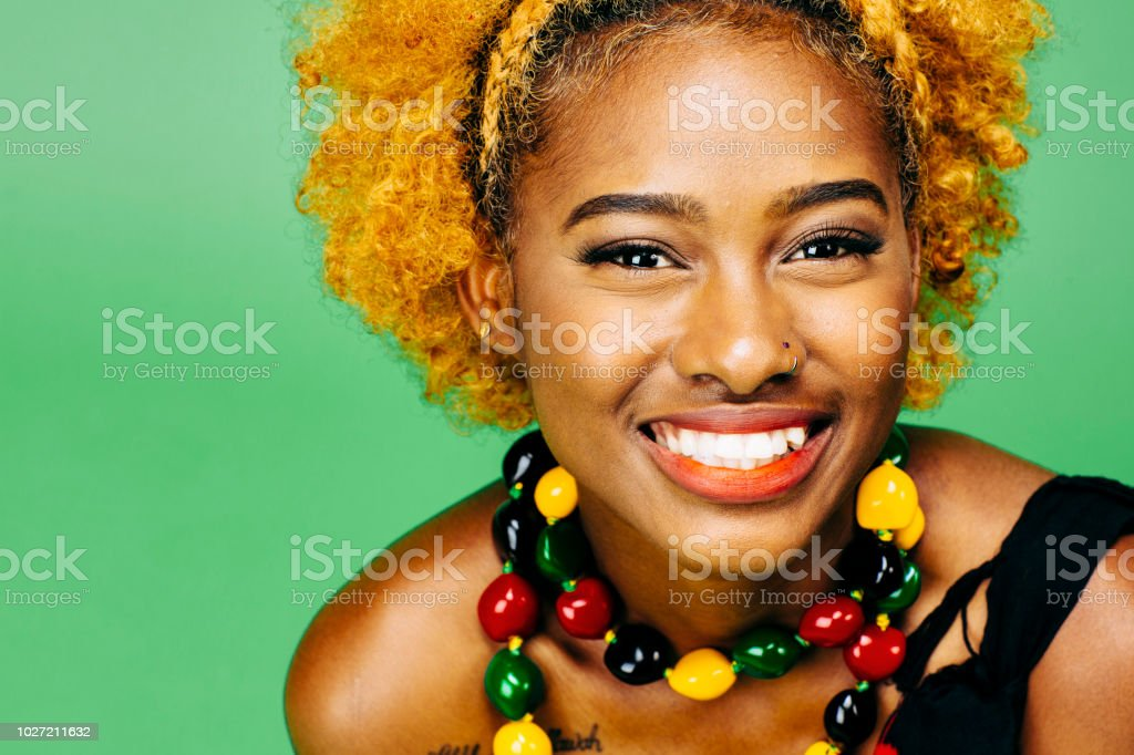 Close up of a very happy young girl with big smile and colorful necklace stock photo