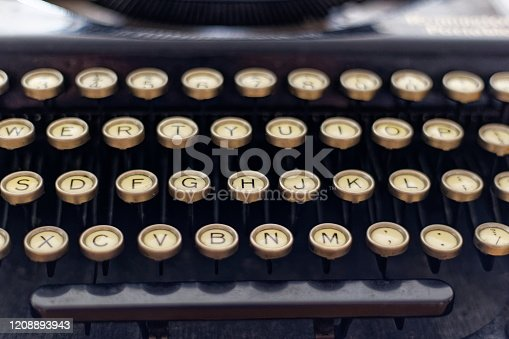 613303142 istock photo Close up of a vintage typewriter. Old vintage typewriter, retro machine with white sheet of paper and typed text. An extreme close up of the keys of a vintage typewriter on a dark background 1208893943