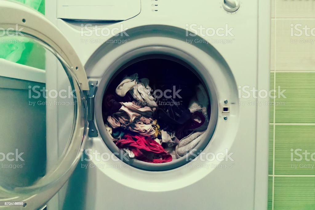 A close up of a washing machine loaded with clothes isolated on white background stock photo