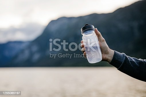 Close up of a reusable water bottle in a hand. Rehydration during activity,  just hand, copy space.
