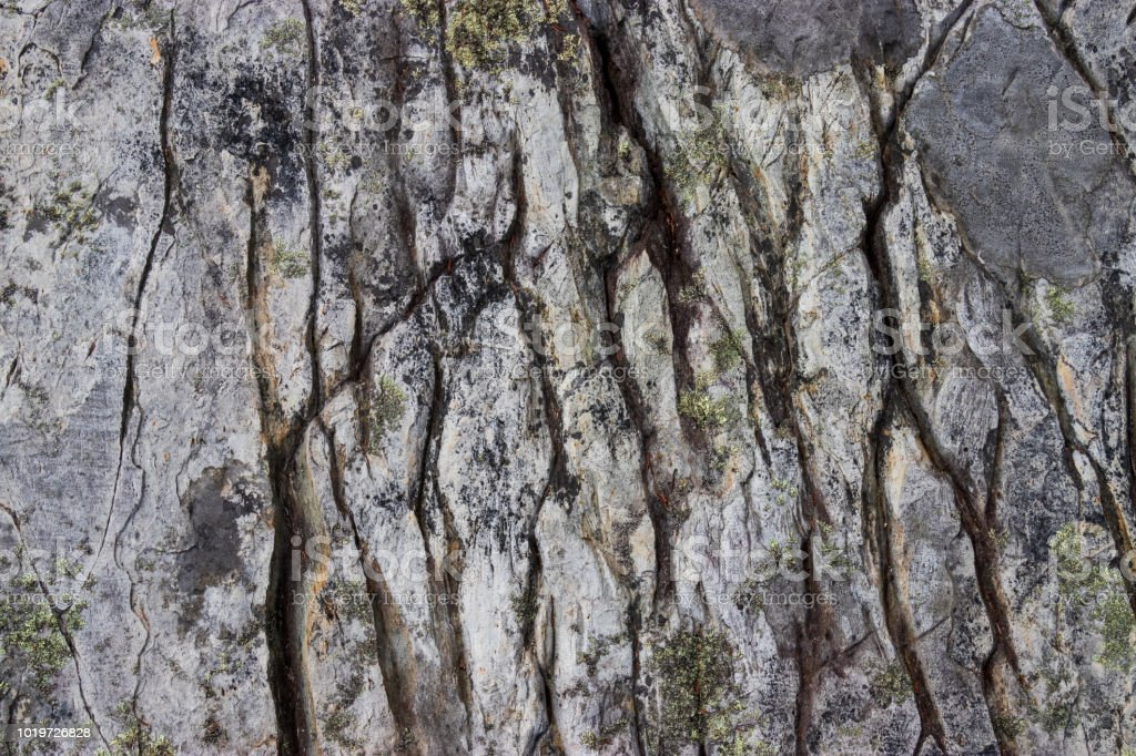 A close up of a weathered rock face with lichen growing on it. stock photo