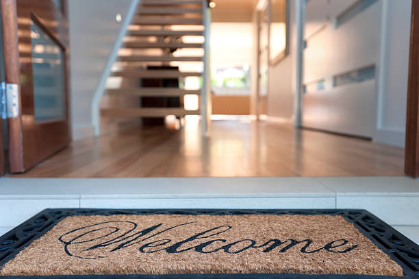 Close up of a welcome mat in an inviting house Close up of a welcome mat in front of an inviting house. Focus on foreground front door stock pictures, royalty-free photos & images
