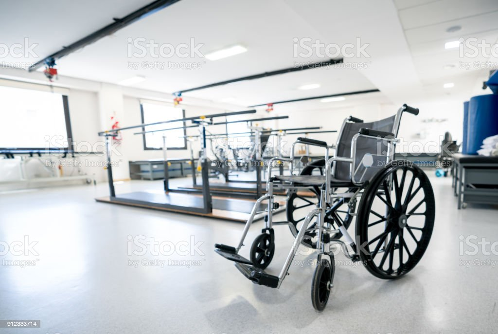 Close up of a wheel chair at a physiotherapy clinic with parallel bars behind stock photo