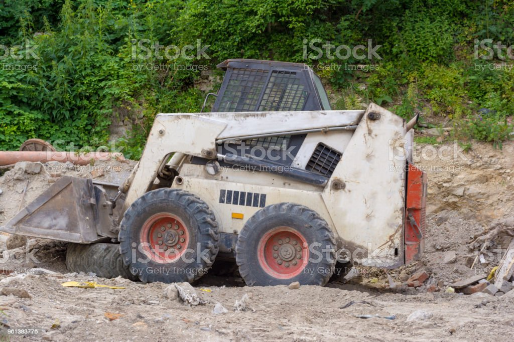 A close up of a white bobcat s550 or skid loader on construction site. stock photo