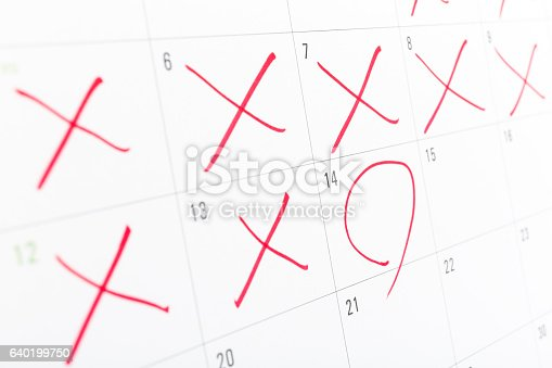 close up of a white calendar page with some of the days crossed off with a red X