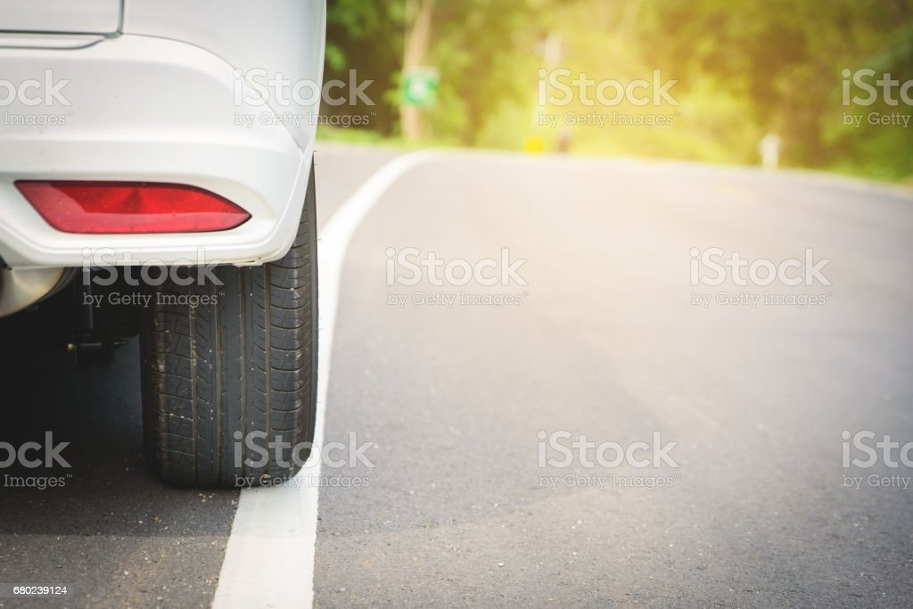 close up of a white car wheel on the ground road with sun light stock photo