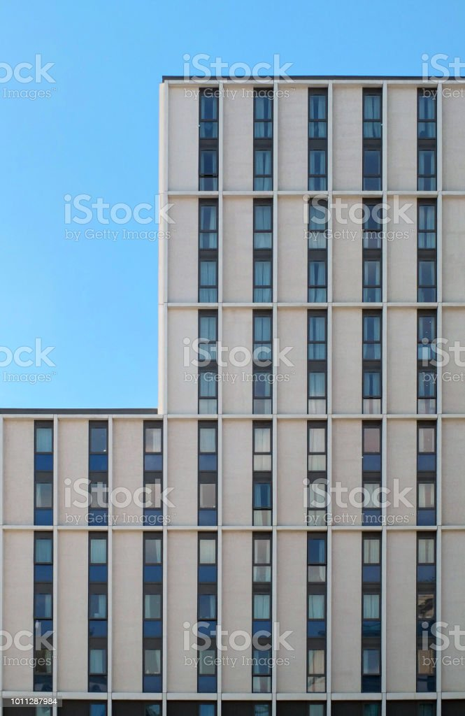 close up of a white modern concrete highrise concrete building with geometrical repeating windows with angular details and corner showing blue sky stock photo