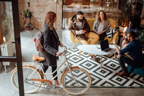 close up of a woman entering office with bicycle - millennial generation stock photos and pictures