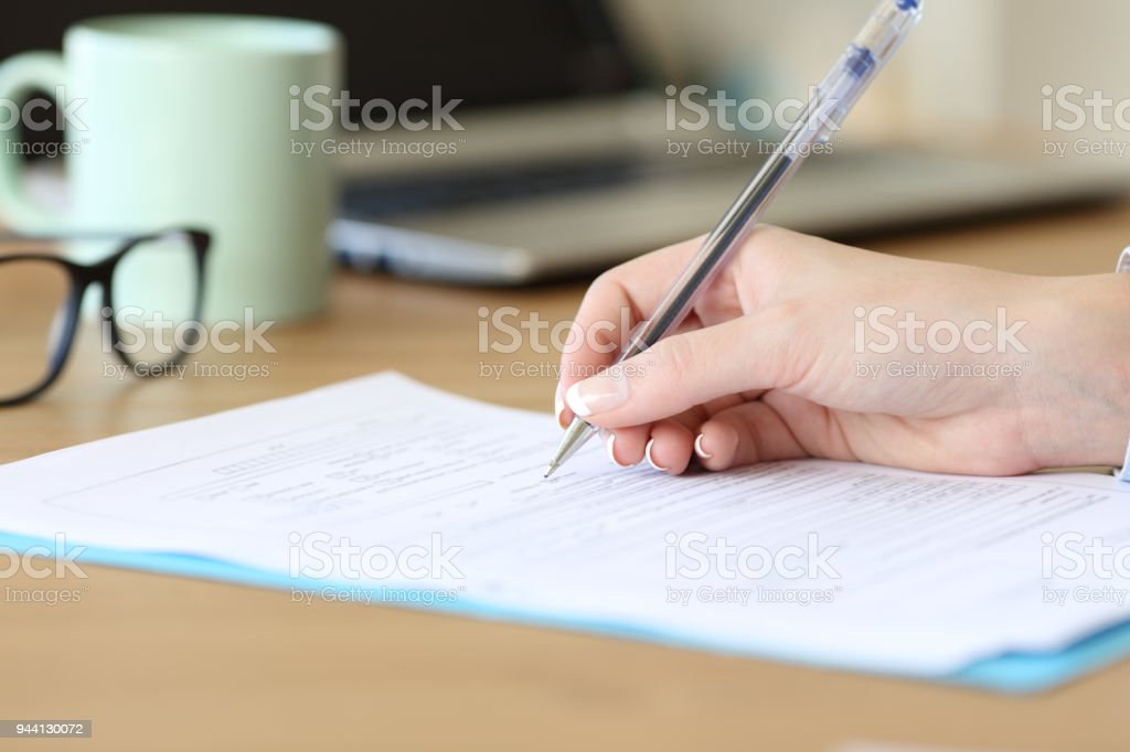 Close up of a woman hand filling form on a table stock photo