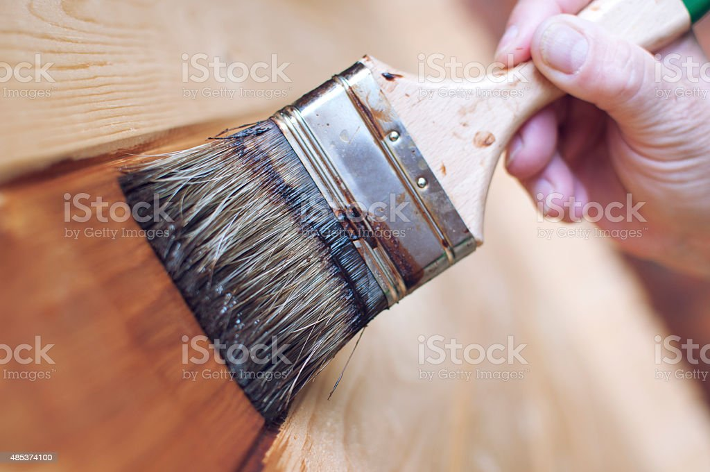 Close up of a woman painting wood with brush stock photo