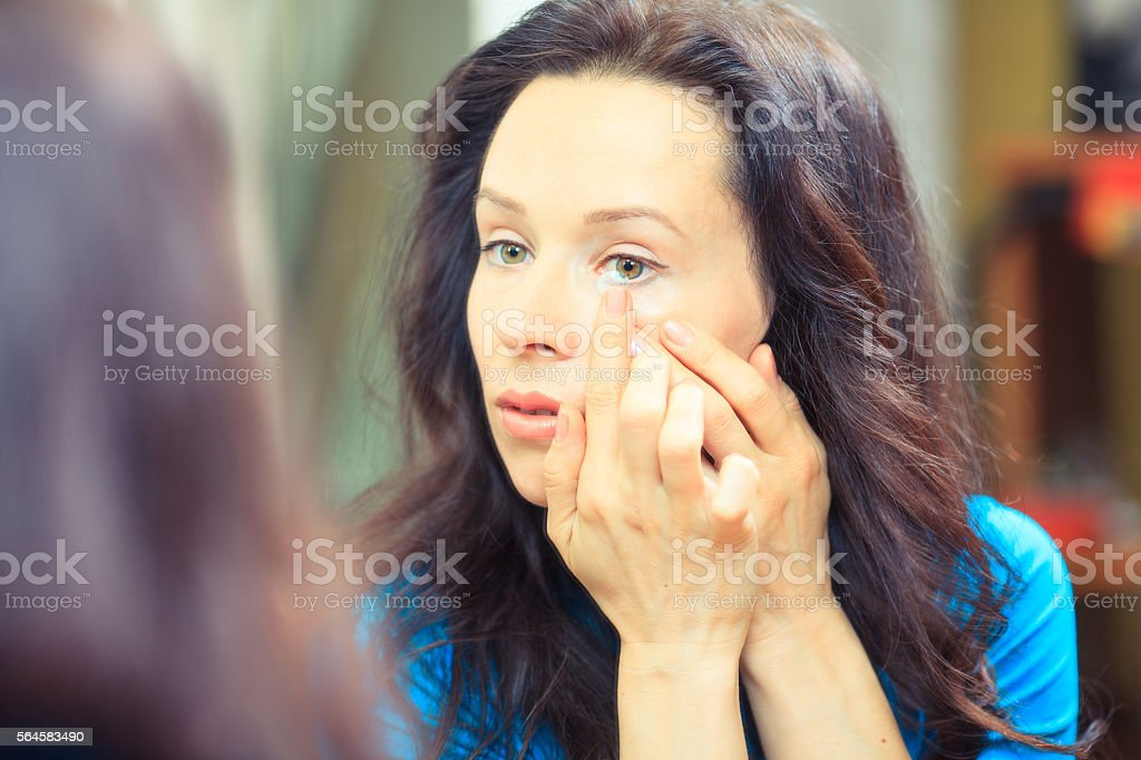 Close up of a woman putting contact lens in eye. stock photo